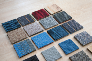 Samples of different Carpet Tiles patterns and colours spread out on wooden floor
