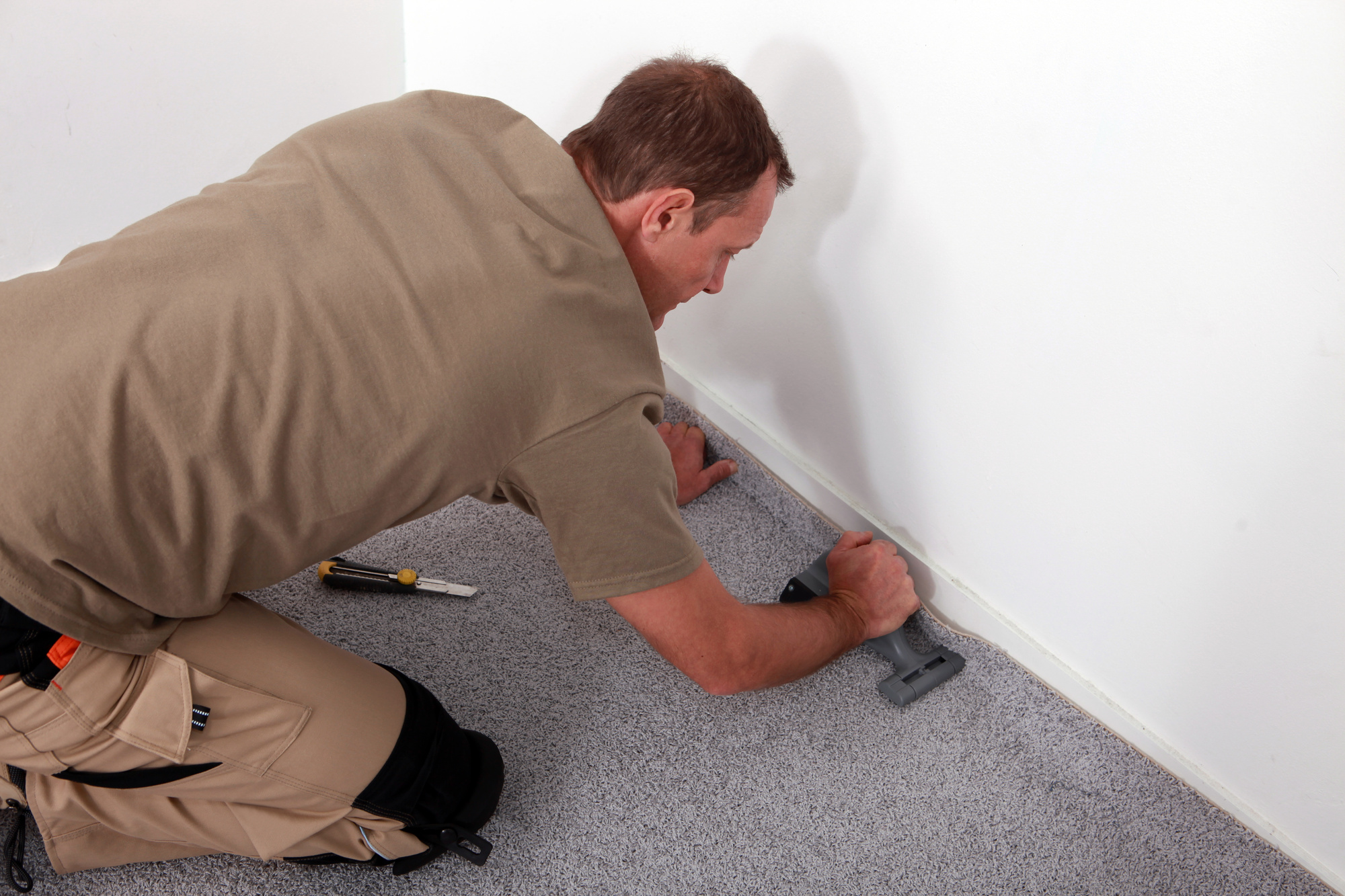 Carpet fitter laying grey carpet over carpet grippers using carpet fitting tools
